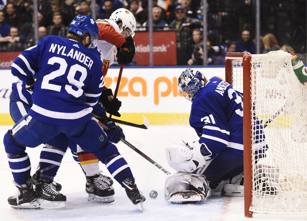 Calgary Flames center Sean Monahan (23) tries to get the puck past Toronto Maple Leafs goalie Frederik Andersen (31) as Maple Leafs center William Nyl
