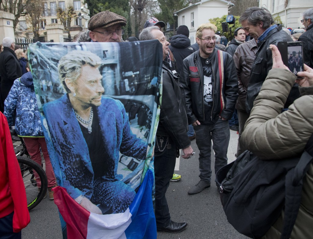 French fan Andre Duval holds a portrait of Johnny Hallyday outside his house in Marnes-la-Coquette, outside Paris, Wednesday, Dec.6, 2017. Johnny Hall