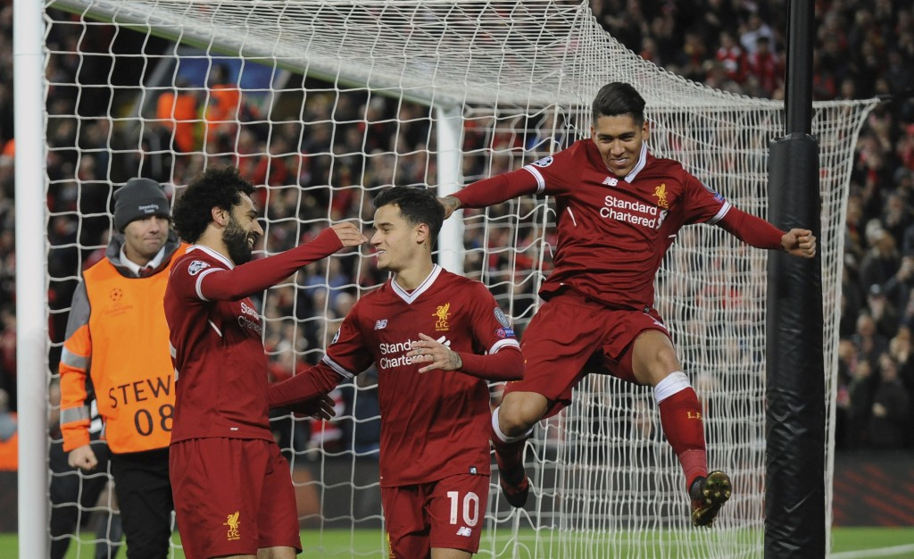 Liverpool's Philippe Coutinho, center, celebrates with his teammates after scoring his side's fifth goal during the Champions League Group E soccer ma