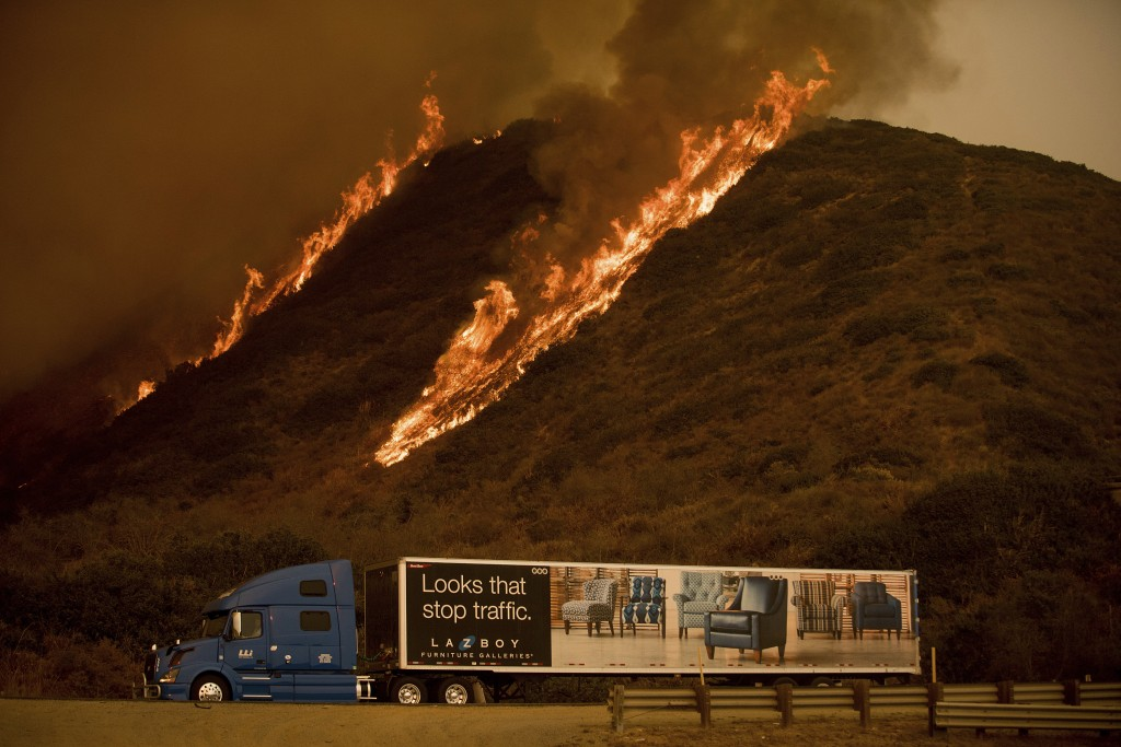 Flames from the Thomas fire burn above a truck on Highway 101 north of Ventura, Calif., on Wednesday, Dec. 6, 2017. (AP Photo/Noah Berger)
