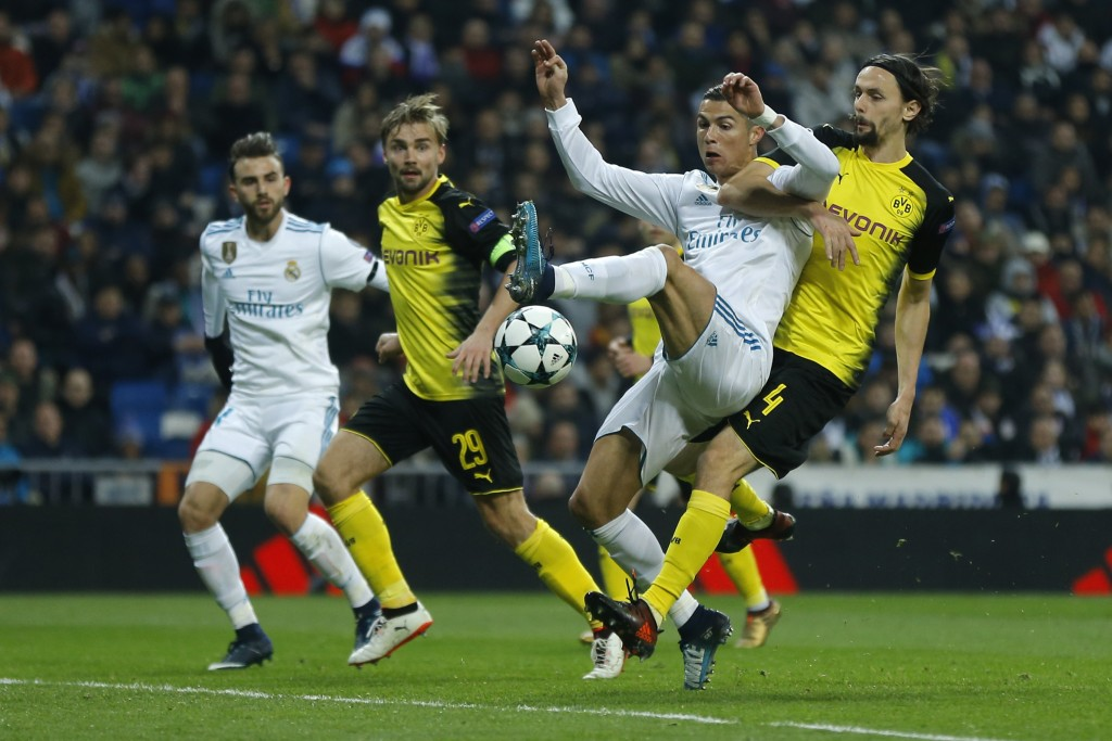 Real Madrid's Cristiano Ronaldo, 2nd right, and Dortmund's Neven Subotic, right, challenge for the ball during the Champions League Group H soccer mat