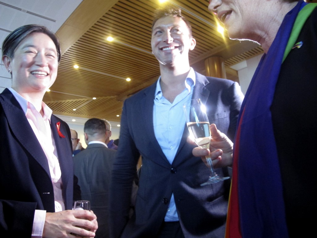 Opposition Labor Party Senator Penny Wong, left, celebrates with former Olympic champion swimmer Ian Thorpe, center,  and Sen. Janet Rice at Parliamen