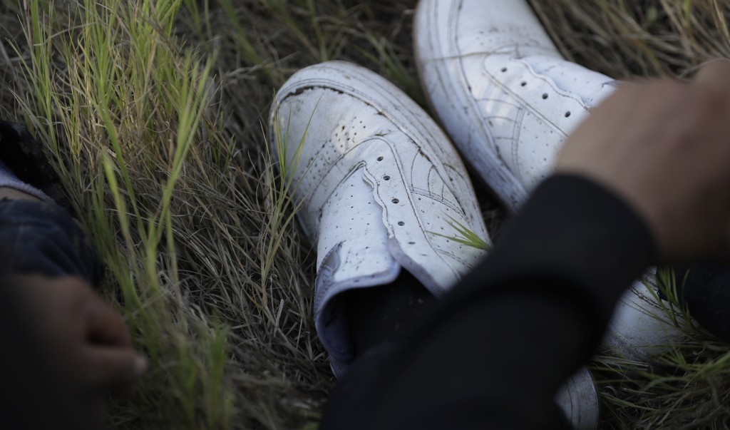 In this Aug. 11, 2017, photo, after having his shoe strings removed, an immigrant suspected of crossing into the United States illegally along the Rio