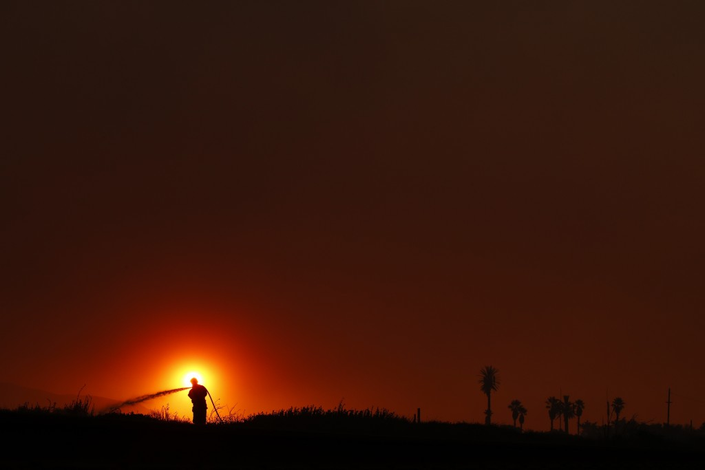 Firefighter Dan Whelan is silhouetted against the sun as he battles a wildfire burning near Faria State Beach in Ventura, Calif., Thursday, Dec. 7, 20