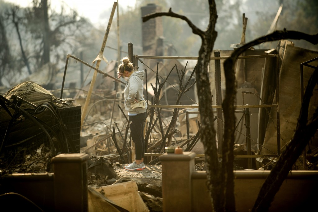 Bree Laubacher pauses while sifting through rubble at her Ventura, Calif., home following a wildfire on Wednesday, Dec. 6, 2017. A barbecue smoker and