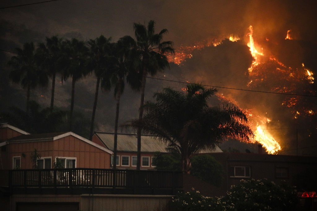 A wildfire threatens homes as it burns along a hillside in La Conchita, Calif., Thursday, Dec. 7, 2017. The wind-swept blazes have forced tens of thou