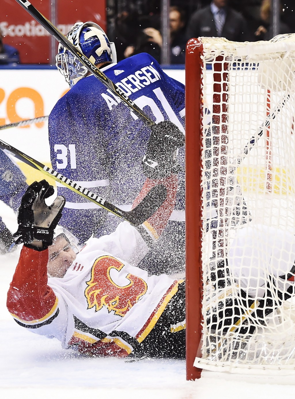 Calgary Flames right wing Garnet Hathaway (21) slides into Toronto Maple Leafs goalie Frederik Andersen's (31) net during the first period of an NHL h