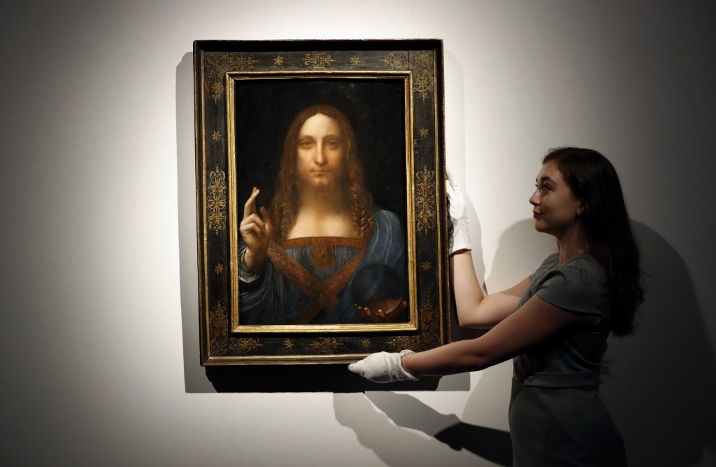 """FILE- In this Oct. 24, 2017 file photo, an employee poses with Leonardo da Vinci's """"Salvator Mundi"""" on display at Christie's auction rooms in London."""