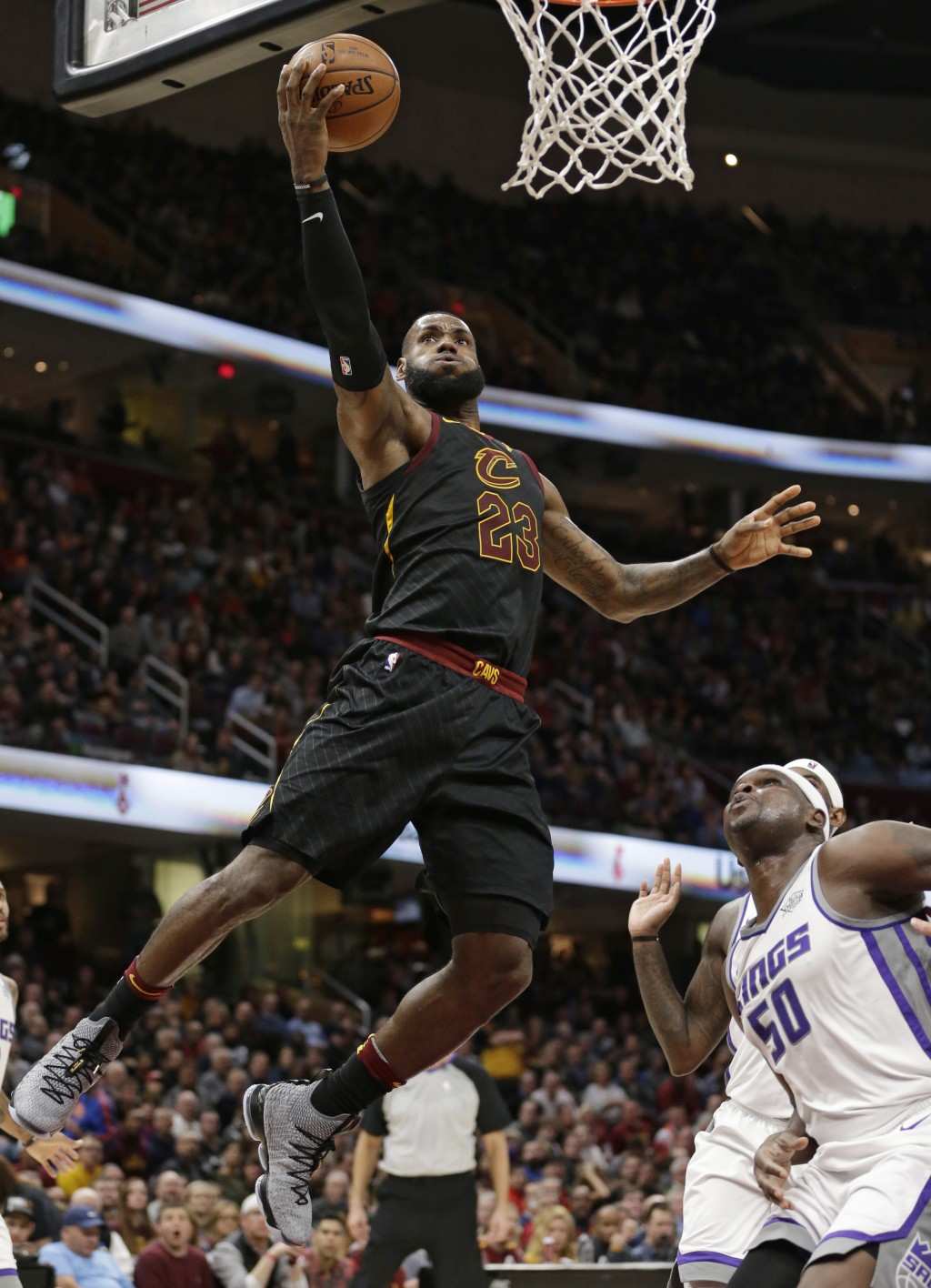 Cleveland Cavaliers' LeBron James (23) drives to the basket against Sacramento Kings' Zach Randolph (50) in the first half of an NBA basketball game,