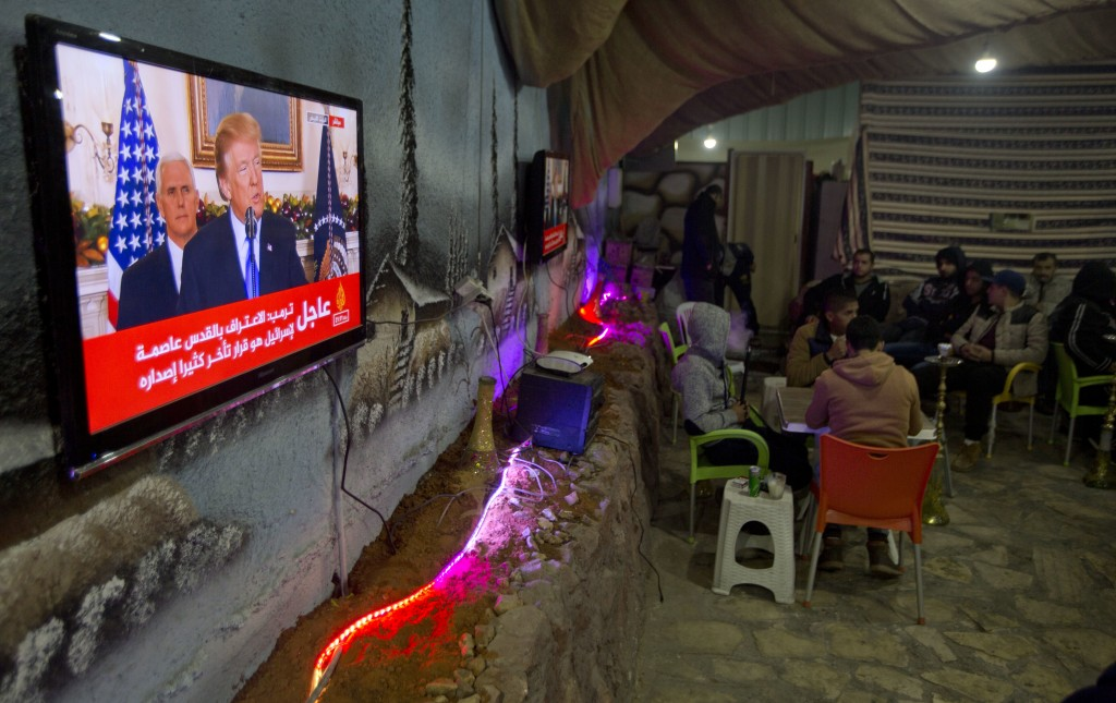 Palestinians play cards during U.S. President Donald Trump's televised speech in the West Bank City of Nablus, Wednesday, Dec. 6, 2017. Defying dire,