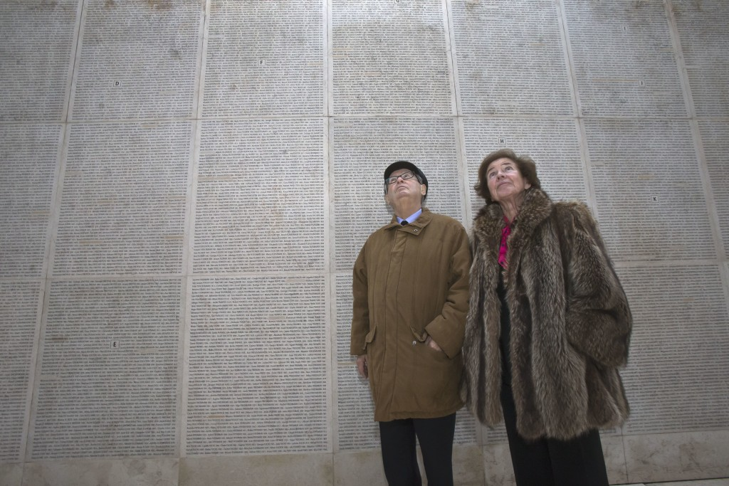 In this photo taken on Tuesday, Dec. 5, 2017 French Nazi hunters Serge Klarsfeld, left, and his wife Beate look at the Wall of Names at the Shoah Memo