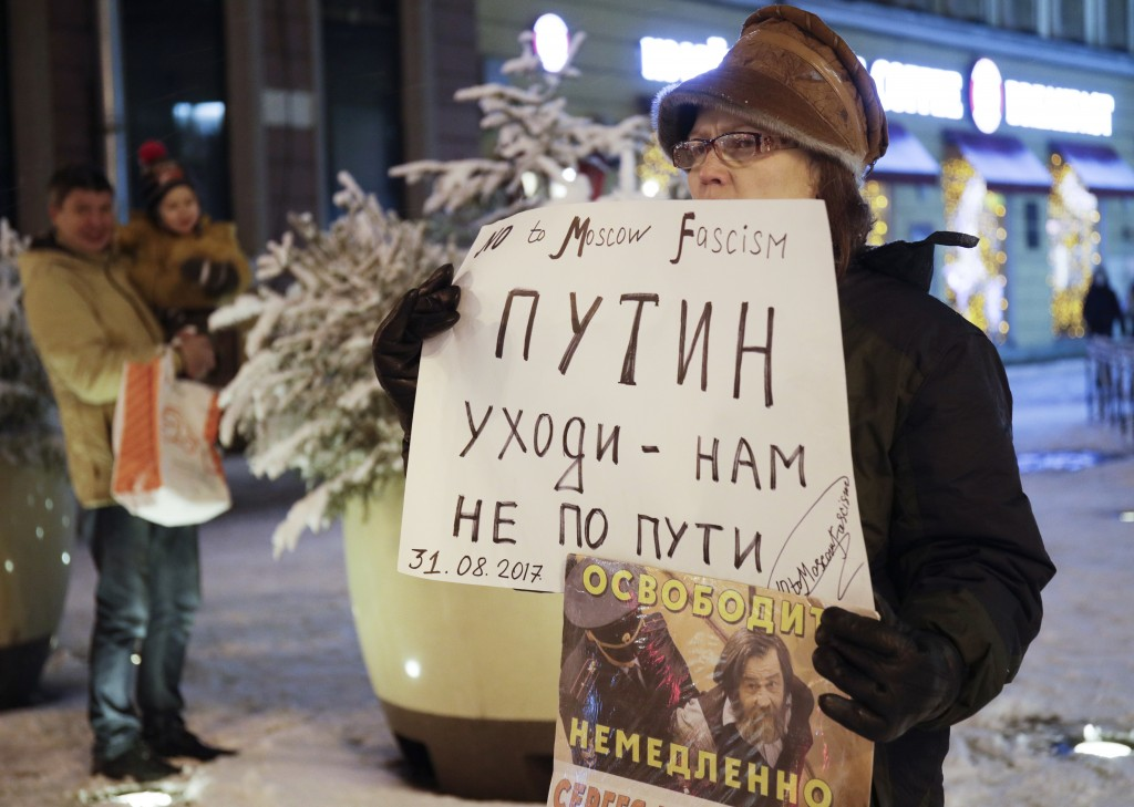 A protester stands in a one-person picket, holding a poster reading 'Putin go away-we do not follow your path!' in St.Petersburg, Russia, Wednesday, D
