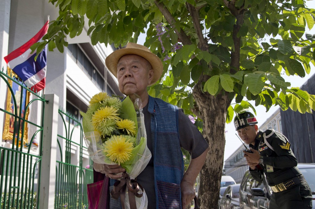 Sulak Sivaraksa pauses outside a military court Thursday, Dec. 7, 2017 in Bangkok, Thailand as he walks in to find out whether military prosecutor has