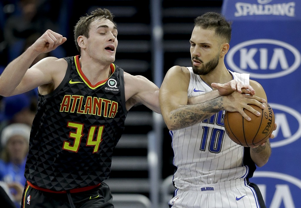 Atlanta Hawks' Tyler Cavanaugh (34) reaches under the arm of Orlando Magic's Evan Fournier (10) as he tries to steal the ball during the first half of