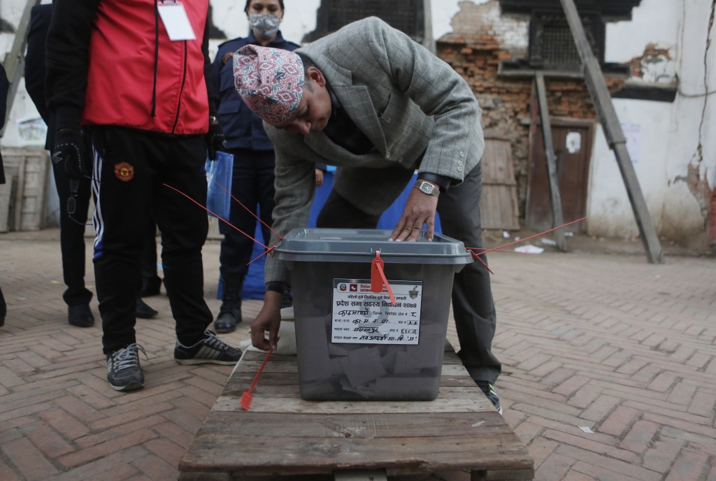 Nepalese election officials seal the ballot box after voting ended at a polling station in Kathmandu, Nepal, Thursday, Dec. 7, 2017. Millions of peopl