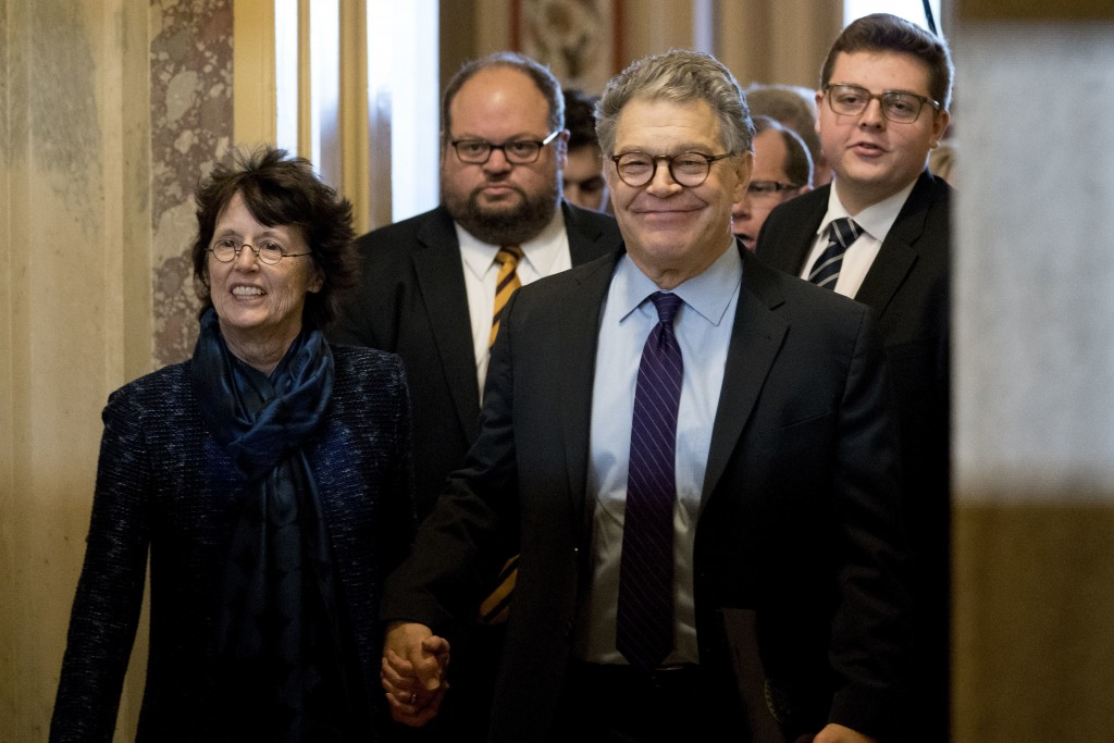 Sen. Al Franken, D-Minn., second from right, holds hands with his wife Franni Bryson, left, as he leaves the Capitol after speaking on the Senate floo