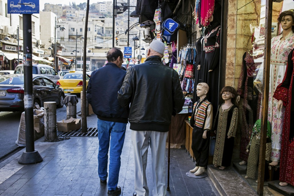 In this Saturday, Dec. 2, 2017 photo, two men walk past shops in downtown Amman, Jordan. A shiny new high-tech utopian city is planned to rise from Jo