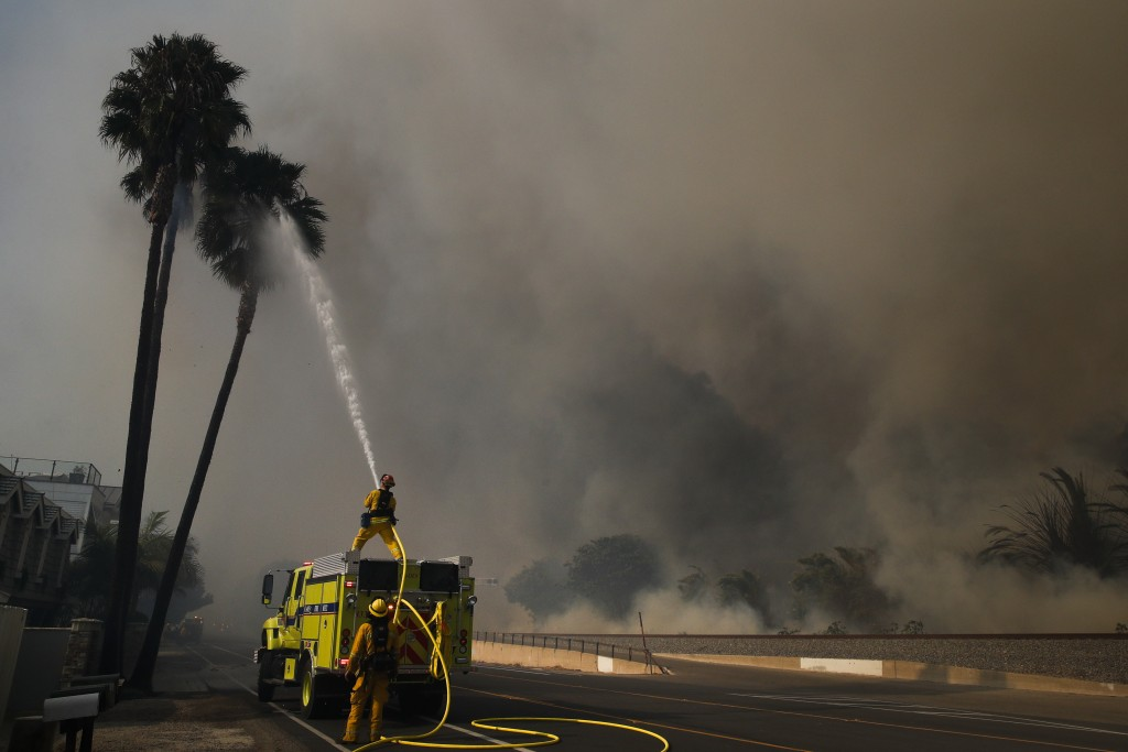 Firefighters battle a wildfire as smoke rises from burning palm trees at Faria State Beach in Ventura, Calif., Thursday, Dec. 7, 2017. The wind-swept