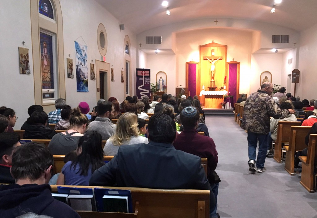 People gather for a vigil at St. Joseph Church in Aztec, N.M., Thursday, Dec. 7, 2017,  Students hid in their classrooms, some behind locked doors or