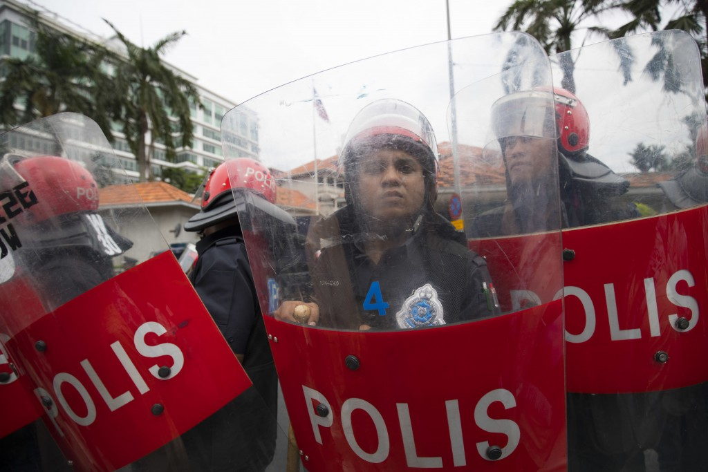 Police stand guard in front of the U.S. Embassy in Kuala Lumpur, Malaysia, Friday, Dec. 8, 2017. Malaysian Muslims, including members of the ruling pa