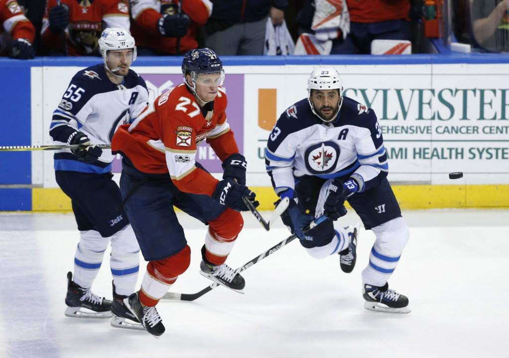 Florida Panthers center Nick Bjugstad (27) and Winnipeg Jets defenseman Dustin Byfuglien (33) and center Mark Scheifele (55) compete for the puck duri