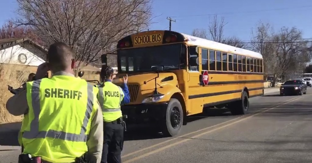 Police escort buses moving students and faculty from Aztec High School after a shooting Thursday, Dec. 7, 2017, in Aztec, N.M. (Jon Austria /The Daily