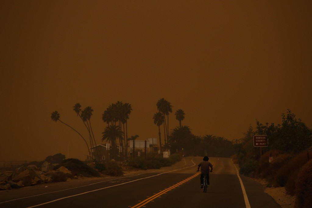 A man rides his bicycle along the Pacific Coast Highway as thick smoke from a massive wildfire fills the air at Faria State Beach in Ventura, Calif.,