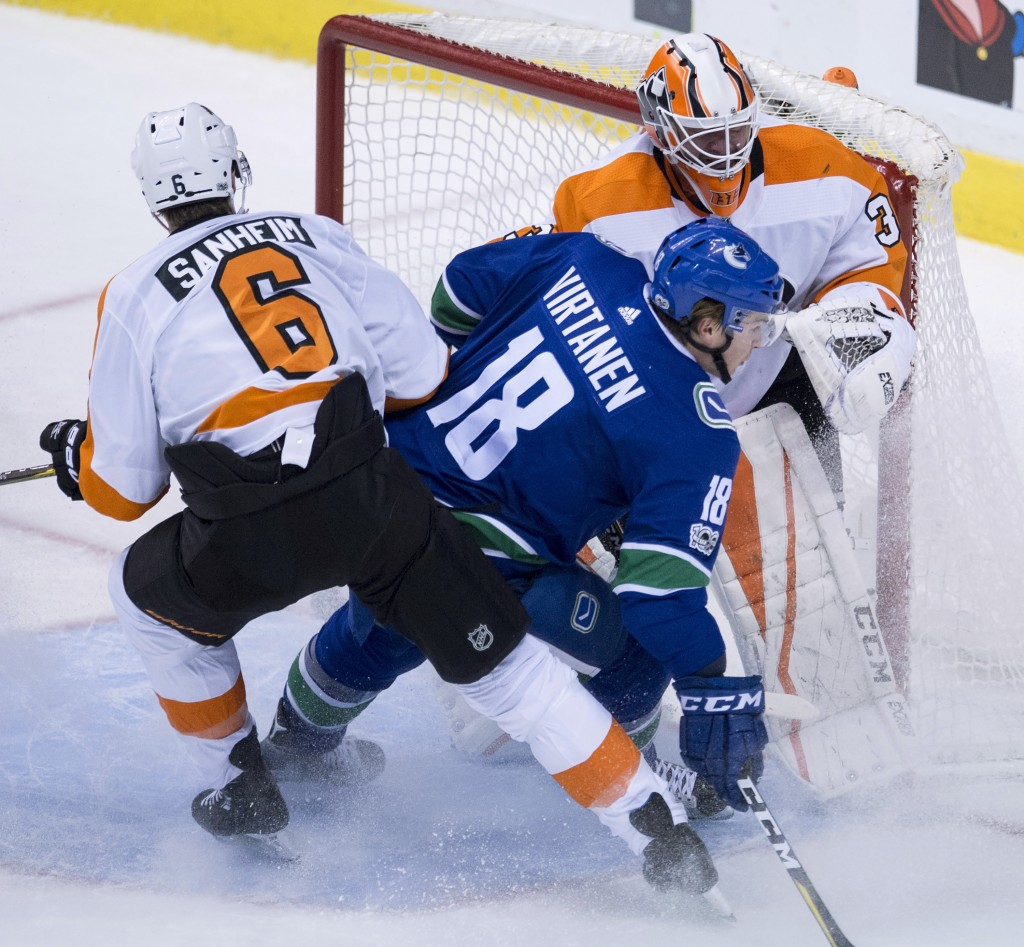 Philadelphia Flyers defenseman Travis Sanheim (6) tries to clear Vancouver Canucks right wing Jake Virtanen (18) from in front of Flyers goalie Brian
