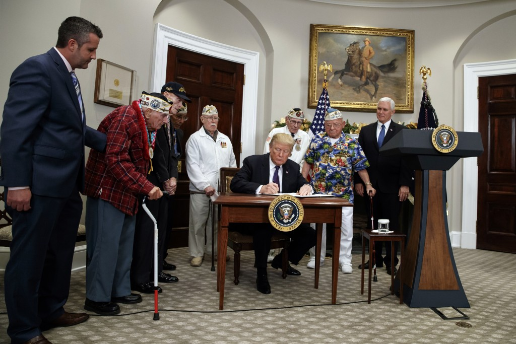 President Donald Trump signs a proclamation for National Pearl Harbor Remembrance Day with survivors of the attack, during an event in the Roosevelt R