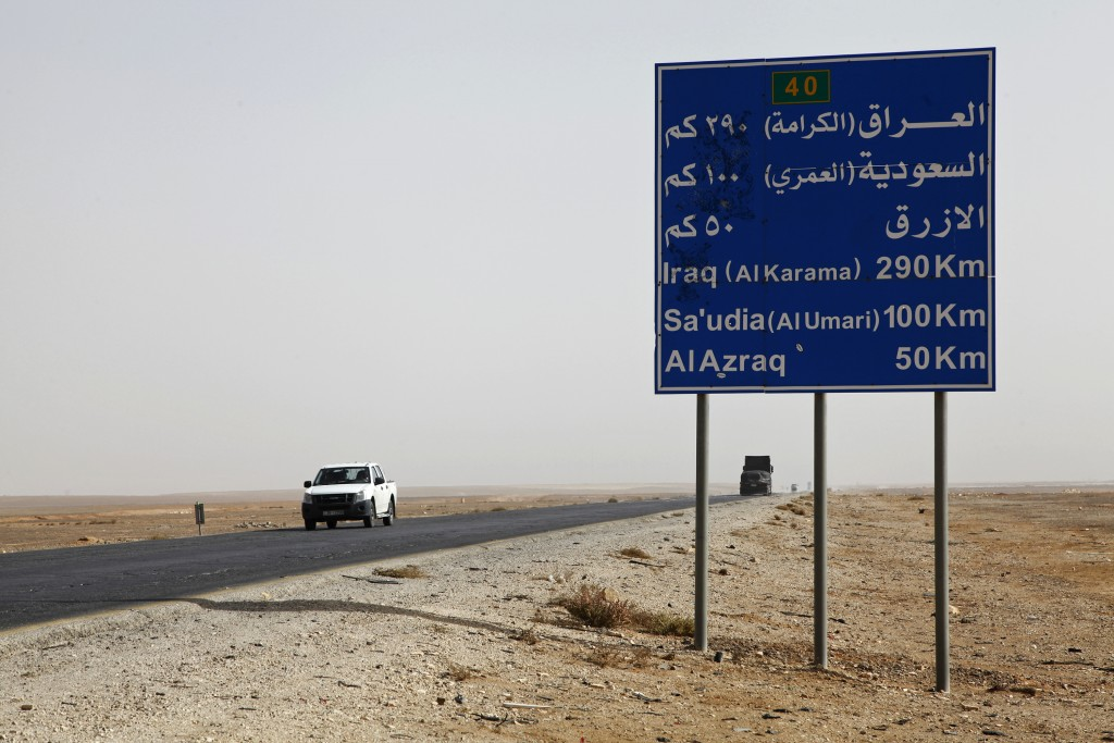 In this Nov. 27, 2017 photo, a car passes a sign on a bleak desert highway where the Jordanian government announced it will build a yet-to-be-named ci