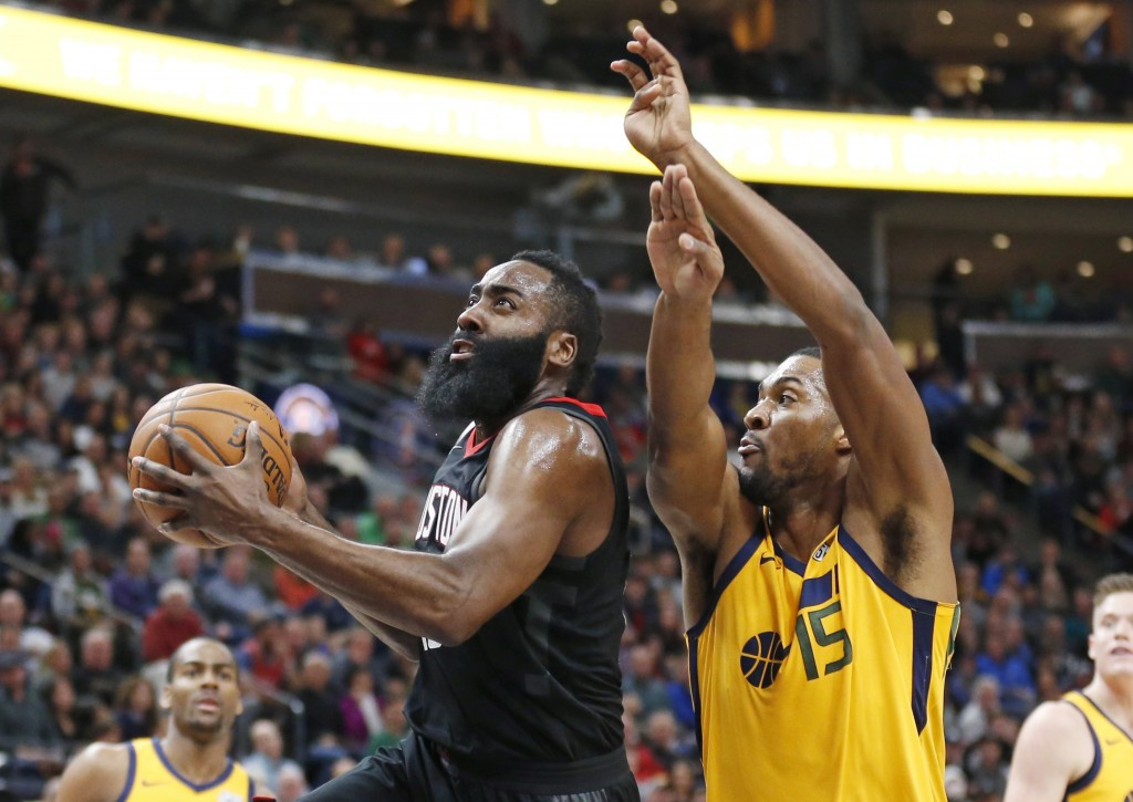 Houston Rockets guard James Harden, left, goes to the basket as Utah Jazz forward Derrick Favors (15) defends during the first half of an NBA basketba