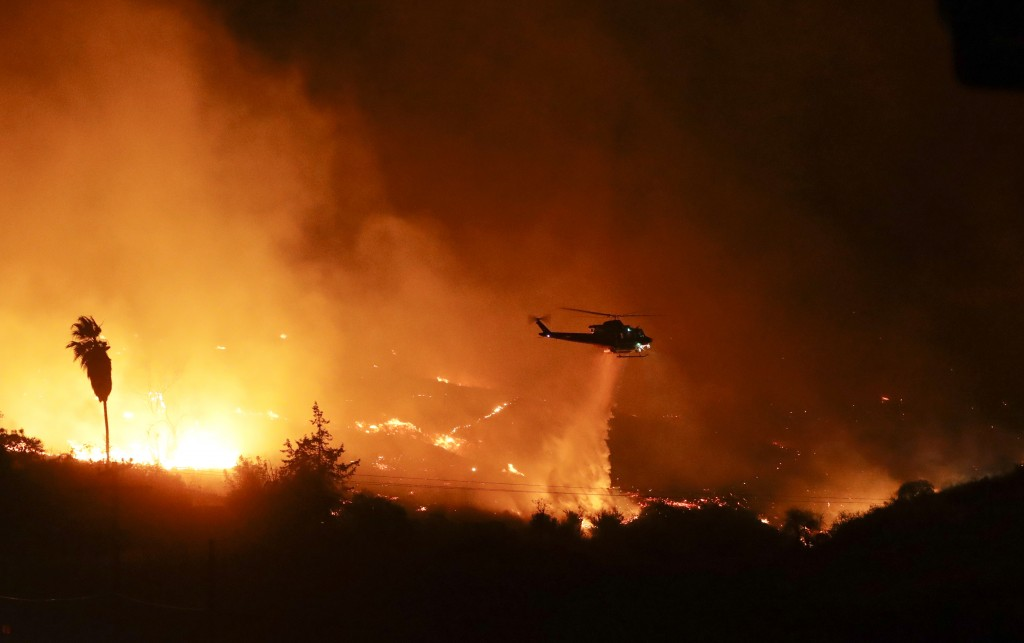 A helicopter drops water over a wildfire Thursday, Dec. 7, 2017, in Bonsall, Calif. The wind-swept blazes have forced tens of thousands of evacuations