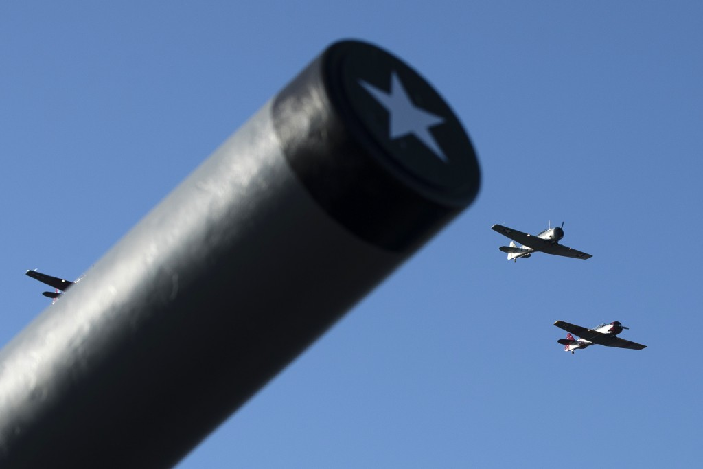 World War II era T-6 Texan trainer aircraft flyover The Battleship New Jersey Museum and Memorial in Camden, N.J., during a ceremony commemorating the