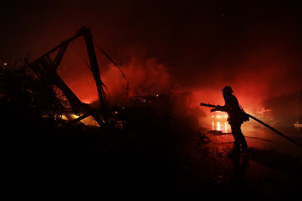 Fire crews work among destroyed homes at the Rancho Monserate Country Club community Thursday, Dec. 7, 2017, in Fallbrook, Calif. The wind-swept blaze