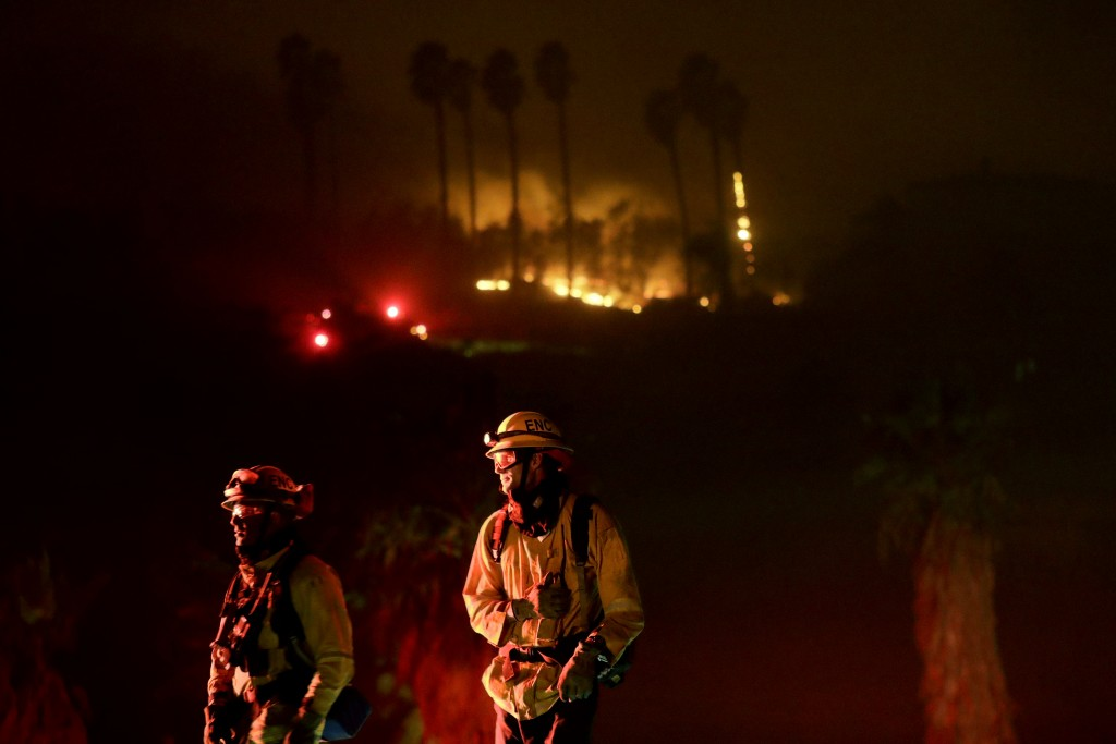 Fire crews look on as they fight a wildfire Thursday, Dec. 7, 2017, in Bonsall, Calif. The wind-swept blazes have forced tens of thousands of evacuati