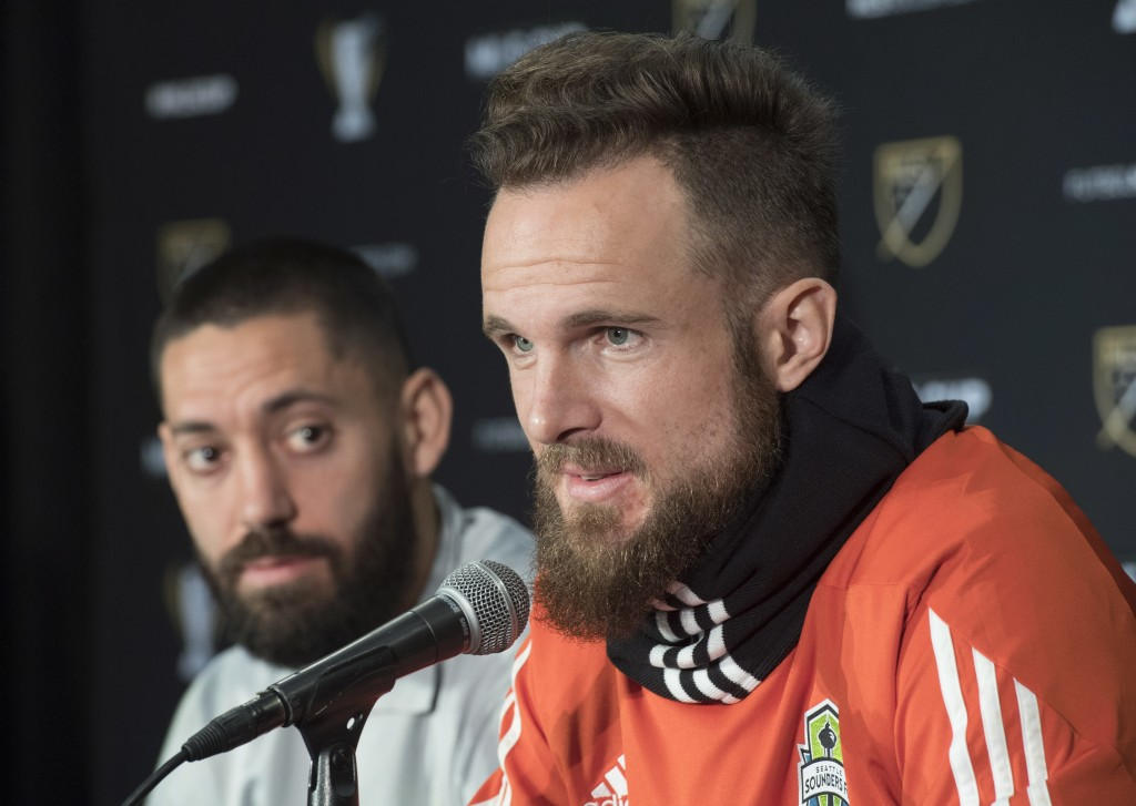 Seattle Sounders goaltender Stefan Frei answers a question as  forward Clint Dempsey listens during a news conference in Toronto, Thursday Dec. 7, 201
