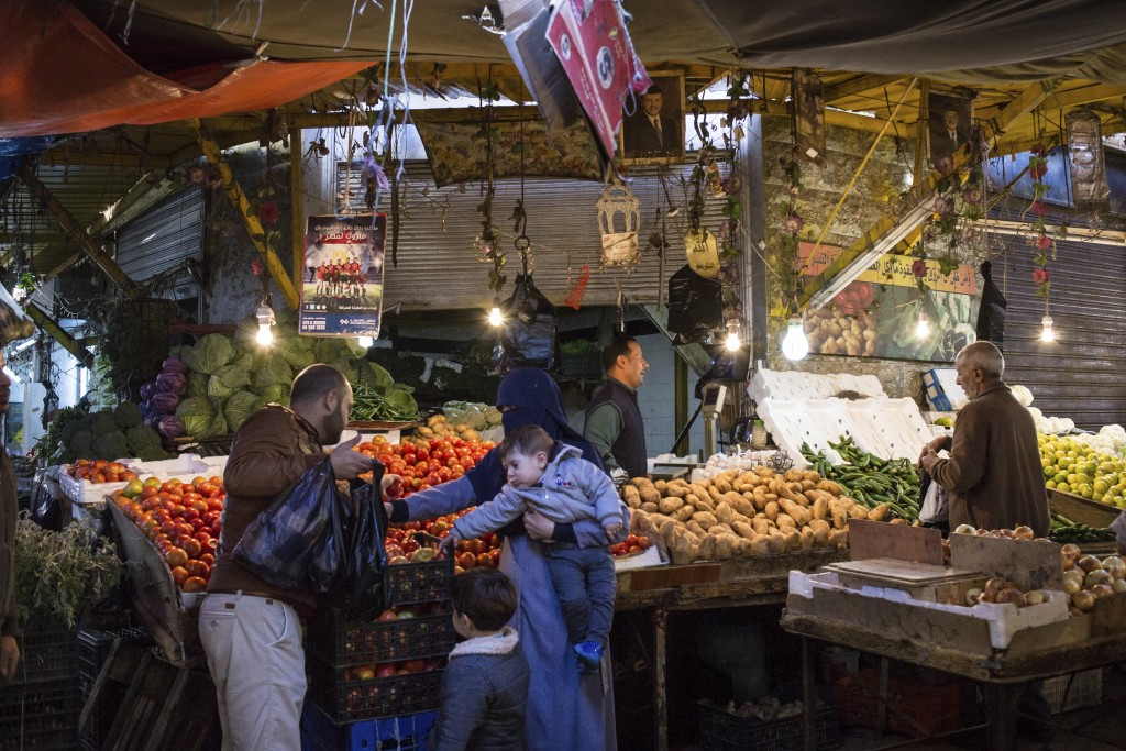 In this Saturday, Dec. 2, 2017 photo, parents with their young children shop for vegetables in downtown Amman, Jordan. A shiny new high-tech utopian c