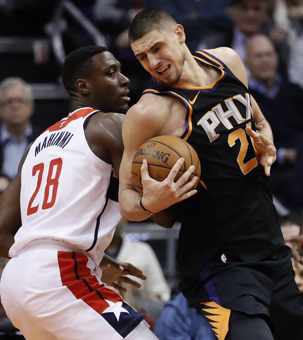 Phoenix Suns center Alex Len (21) spins around Washington Wizards center Ian Mahinmi (28) during the first half of an NBA basketball game, Thursday, D