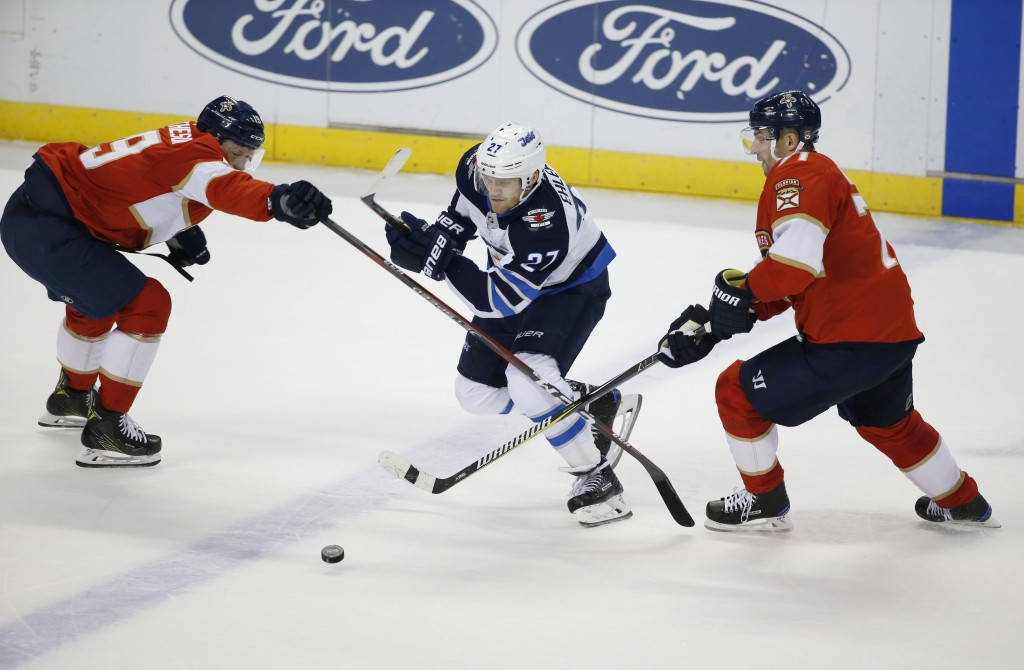 Winnipeg Jets center Adam Lowry (17) battles for the puck with Florida Panthers right wing Radim Vrbata, right, and defenseman Mike Matheson during th