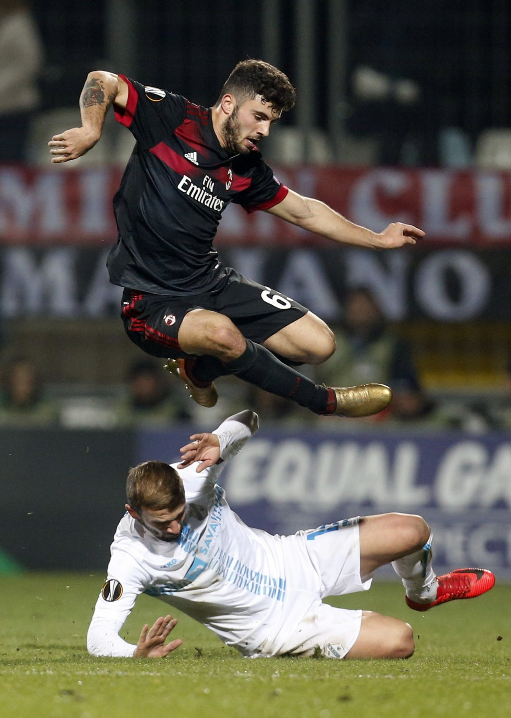 Milan's Patrick Cutrone, top, jumps over Rijeka's Dario Zuparic during the group D Europa League soccer match between Rijeka and Milan, at the Rujevic