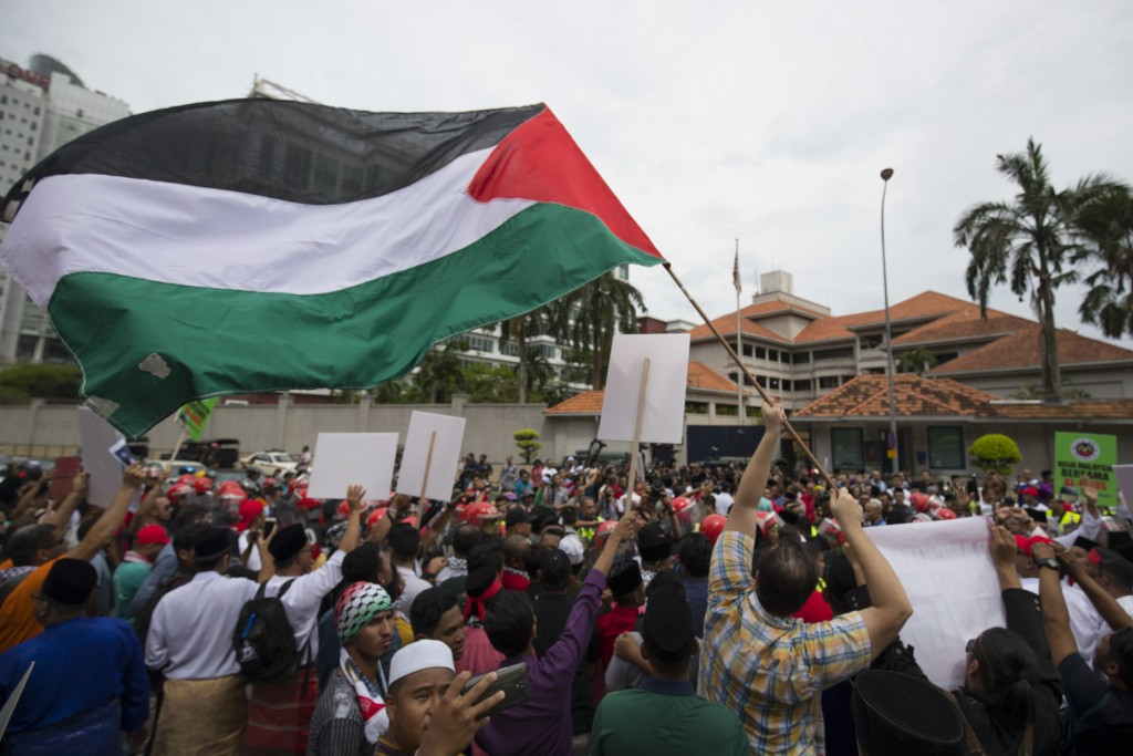 Protesters waves Palestine flags during a protest outside the U.S. Embassy in Kuala Lumpur, Malaysia, Friday, Dec. 8, 2017. Malaysian Muslims, includi