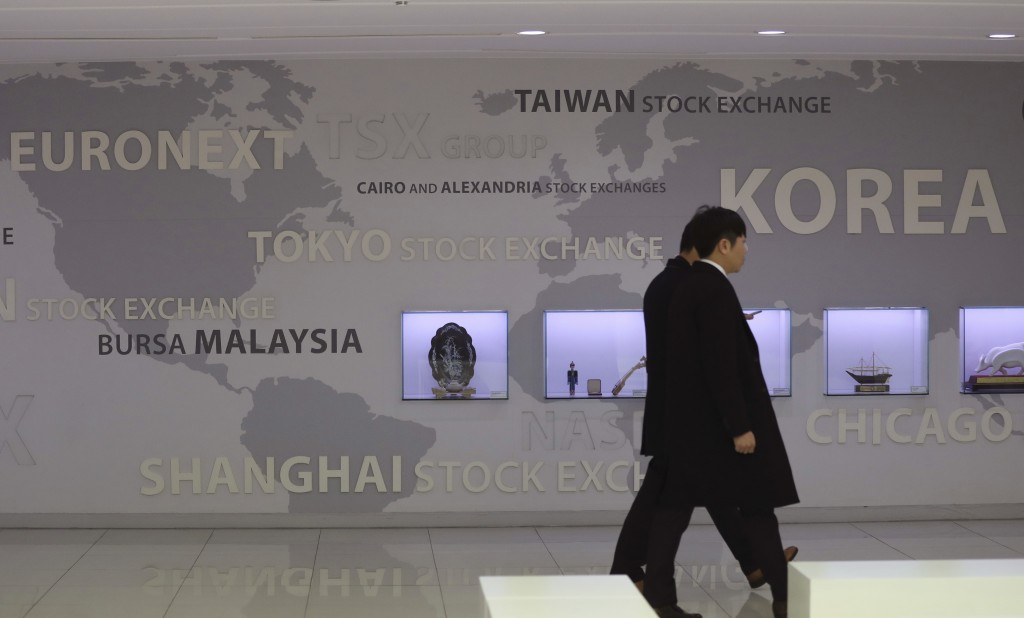 Men walk by the signboard of world stock exchange at the Korea Exchange in Seoul, South Korea, Friday, Dec. 8, 2017. Asian share indexes advanced Frid