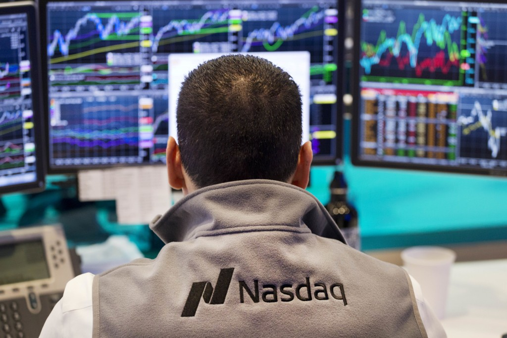 FILE - In this April 16, 2015, file photo, an employee monitors prices at the tech-driven Nasdaq MarketSite in New York. From Silicon Valley to Shangh