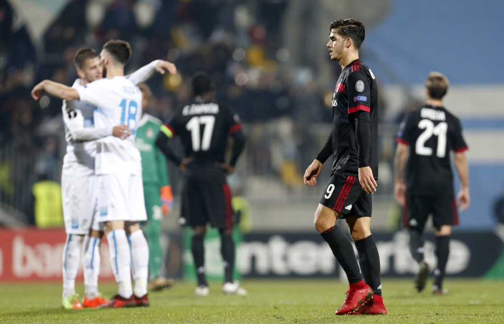 Milan's Andre Silva, right, walks past jubilating Rijeka players at the end of the group D Europa League soccer match between Rijeka and Milan, at the