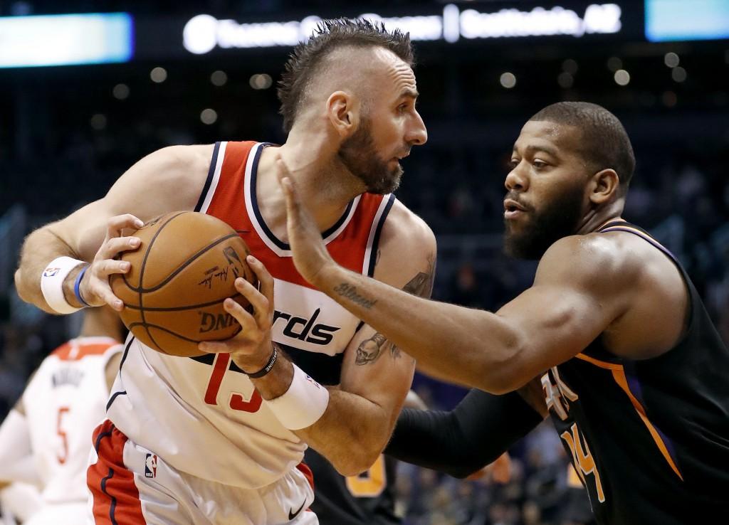 Washington Wizards center Marcin Gortat (13) looks to pass as Phoenix Suns center Greg Monroe (14) defends during the first half of an NBA basketball