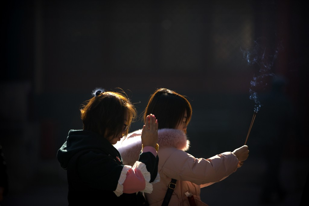 Visitors hold incense sticks as they pray at the Yonghegong Lama Temple in Beijing, Friday, Dec. 8, 2017. The temple complex, which dates from the Qin
