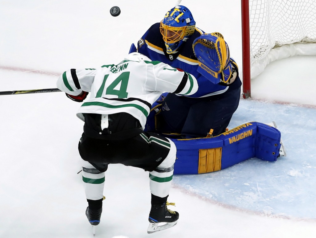 St. Louis Blues goalie Jake Allen, right, watches the puck after it bounced off Dallas Stars' Jamie Benn (14) during the second period of an NHL hocke