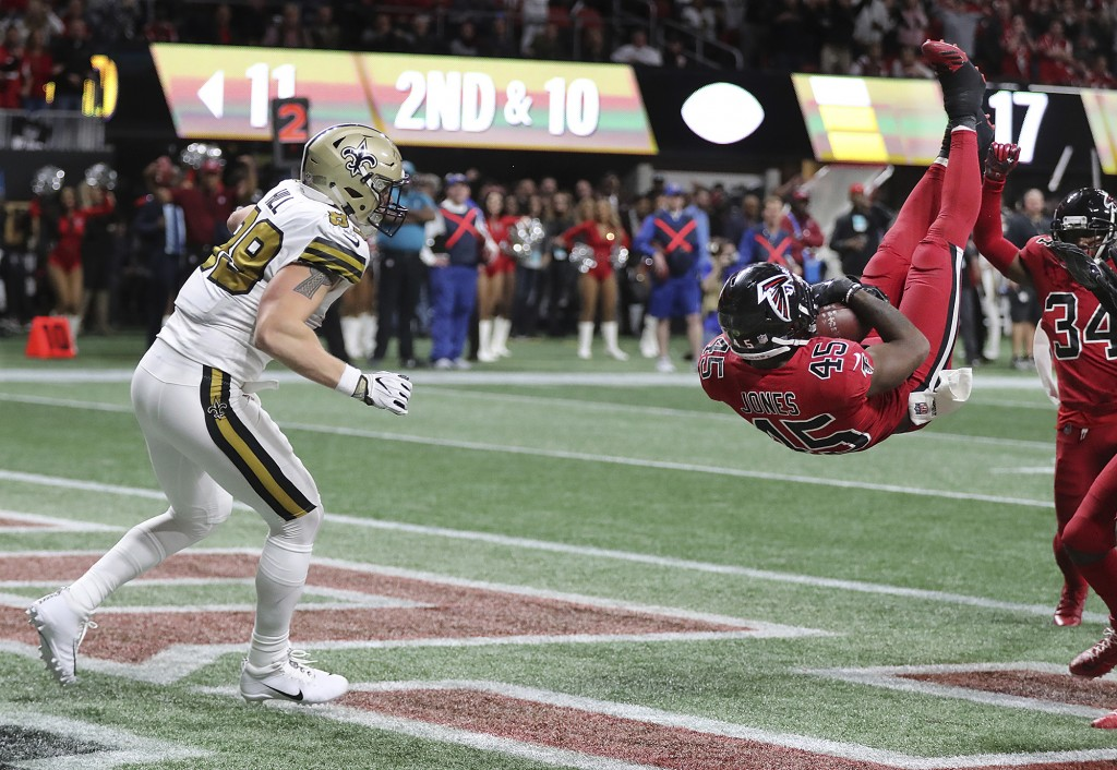 Atlanta Falcons linebacker Deion Jones intercepts a pass from New Orleans Saints quarterback Drew Brees intended for tight end Josh Hill, left, in the
