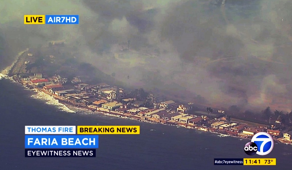 This aerial view from video provided by KABC-TV shows flames from a wildfire bearing down on homes on Faria Beach just outside Ventura, Calif., Thursd