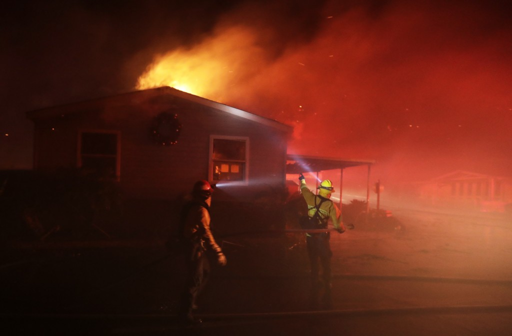 Fire crews work among burning homes at the Rancho Monserate Country Club community Thursday, Dec. 7, 2017, in Fallbrook, Calif. The wind-swept blazes